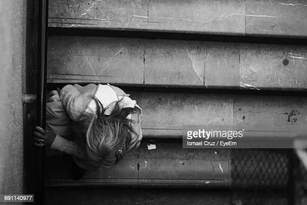 High Angle View Of Homeless Woman Sitting On Steps