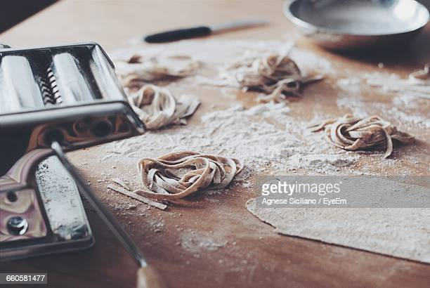 High Angle View Of Homemade Tagliatelle With Pasta Maker On Table