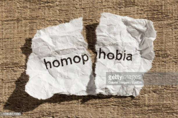 high angle view of homophobia text on torn crumpled paper - homofobia fotografías e imágenes de stock