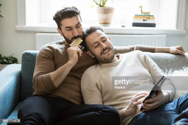 high angle view of homosexual couple doing online shopping while relaxing on sofa at home - house icon stock pictures, royalty-free photos & images