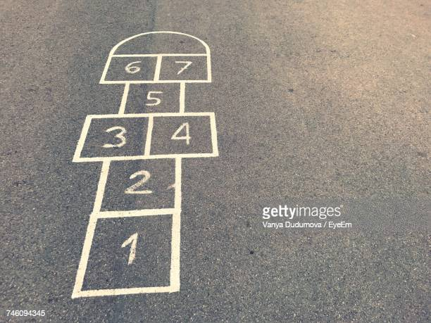 high angle view of hopscotch board drawn on road - hopscotch stock pictures, royalty-free photos & images