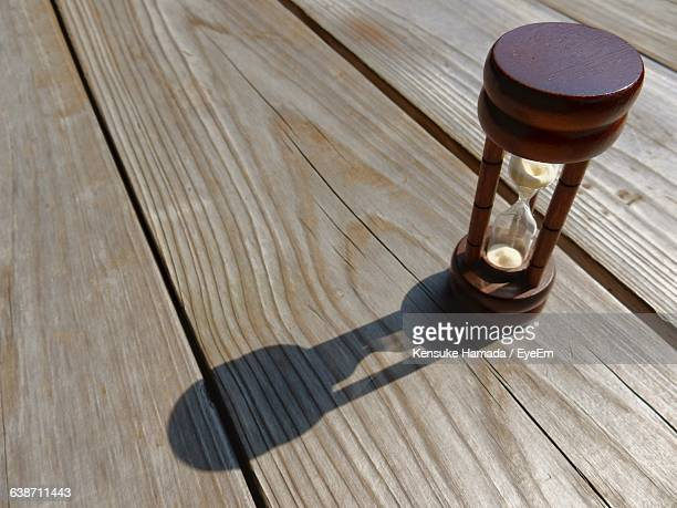 High Angle View Of Hourglass On Wooden Table