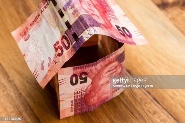 high angle view of house made from paper currencies on wooden table - south african currency stock pictures, royalty-free photos & images