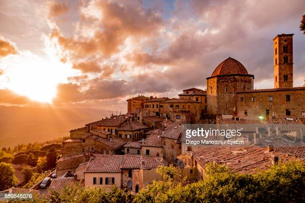 high angle view of houses against cloudy sky - volterra stock photos and pictures