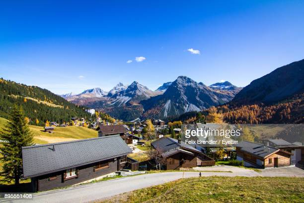high angle view of houses and mountains against blue sky - アロサ ストックフォトと画像