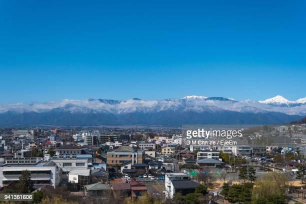 high angle view of houses and mountains against clear blue sky - 長野県 ストックフォトと画像