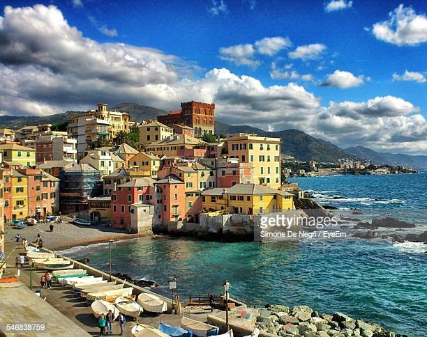 high angle view of houses by lake in boccadasse against cloudy sky - genoa italy stock pictures, royalty-free photos & images