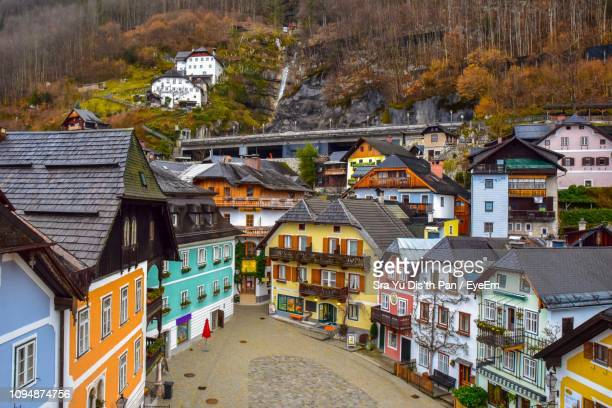 high angle view of houses by road in town - hallstatt stock-fotos und bilder