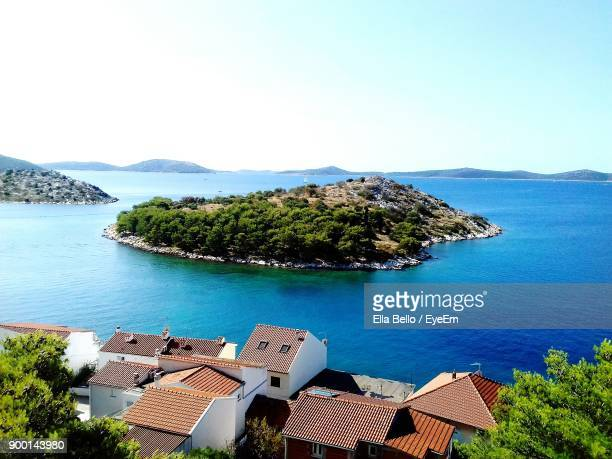 high angle view of houses by sea against clear sky - ella bello stock-fotos und bilder