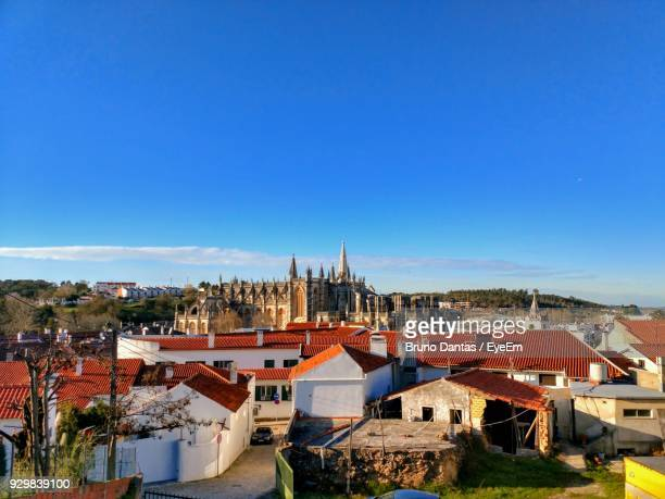 high angle view of houses in town against clear blue sky - estremadura stock-fotos und bilder