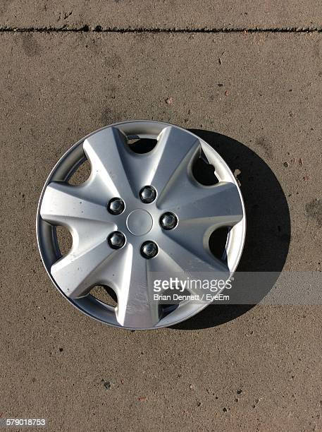High Angle View Of Hubcap On Footpath