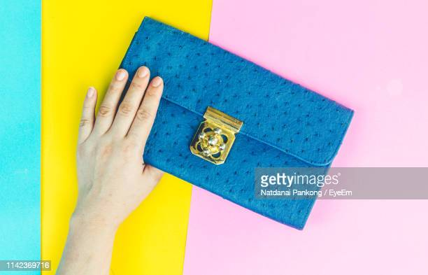 high angle view of human hand holding blue clutch bag over colored background - pochette borsetta foto e immagini stock