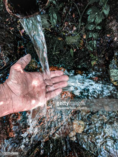 high angle view of human hand on rock touching flowing water - 湧水 ストックフォトと画像