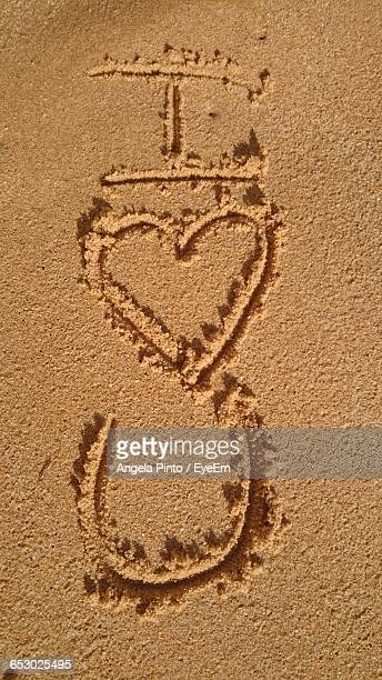 high angle view of i love you text at sandy beach - letter u stock photos and pictures