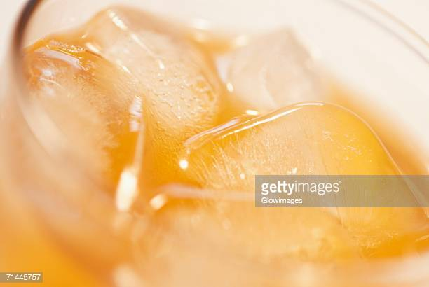 High angle view of ice cubes in a glass of orange juice