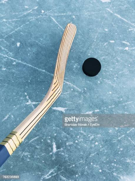 high angle view of ice hockey stick and puck on rink - hockey stick stock pictures, royalty-free photos & images