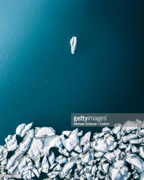 high angle view of icebergs floating on sea during winter - berg stock pictures, royalty-free photos & images