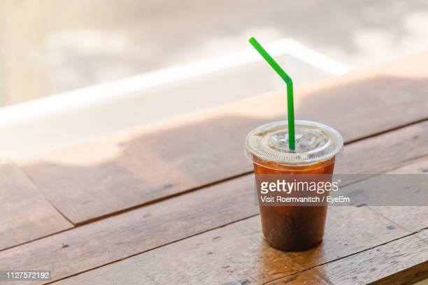 high angle view of iced coffee on wooden table - iced coffee stock pictures, royalty-free photos & images