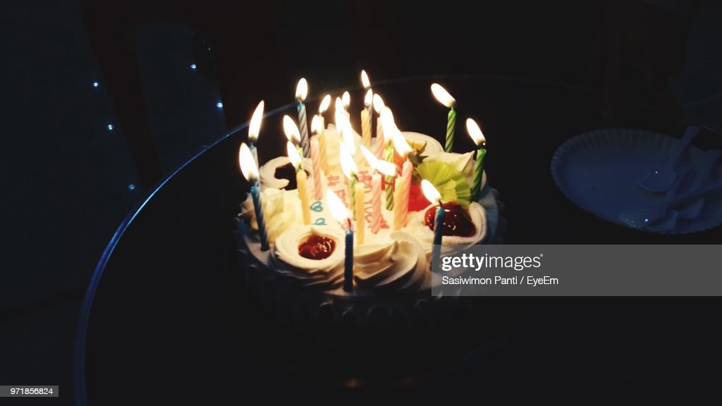 High Angle View Of Illuminated Birthday Cake On Table In Darkroom
