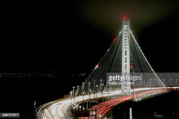 high angle view of illuminated bridge at night - bay bridge stock pictures, royalty-free photos & images