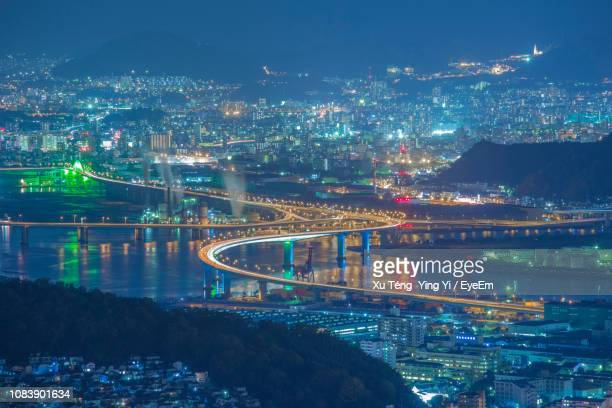 high angle view of illuminated bridge over river and buildings at night - hiroshima imagens e fotografias de stock