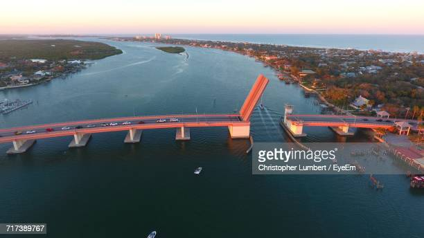 High Angle View Of Illuminated Bridge Over River In City At Sunset
