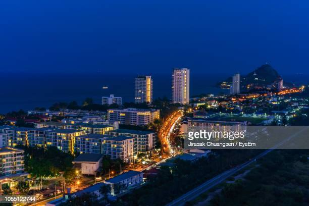 high angle view of illuminated buildings against sky at night - prachuap khiri khan province stock pictures, royalty-free photos & images