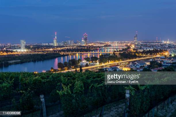 high angle view of illuminated buildings against sky at night - wien stock-fotos und bilder