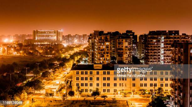 high angle view of illuminated buildings against sky at night - new delhi stock pictures, royalty-free photos & images