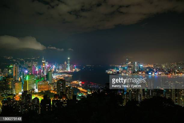 high angle view of illuminated buildings against sky at night - etalement urbain photos et images de collection