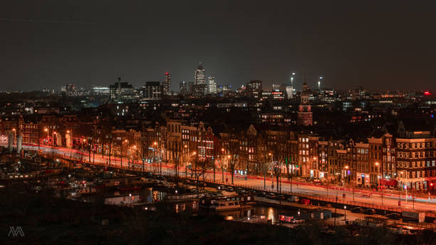 high angle view of illuminated buildings against sky at night - amsterdam night stock pictures, royalty-free photos & images