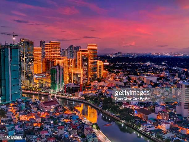 high angle view of illuminated buildings against sky during sunset - greater manila area stock-fotos und bilder