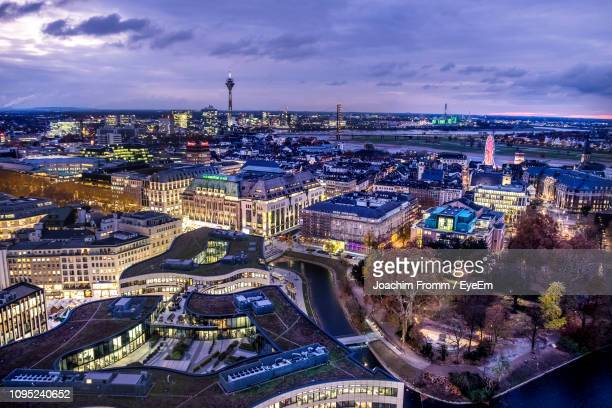 high angle view of illuminated buildings by river against sky - düsseldorf stock pictures, royalty-free photos & images