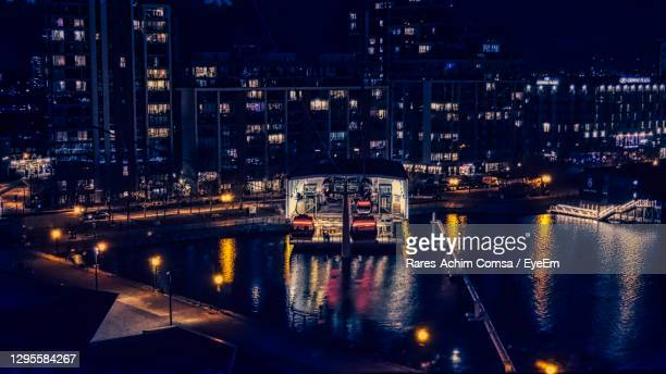 high angle view of illuminated buildings by river at night - the o2 england stock pictures, royalty-free photos & images