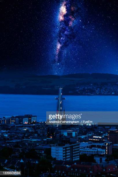 high angle view of illuminated buildings by sea against sky at night - space and astronomy stock pictures, royalty-free photos & images