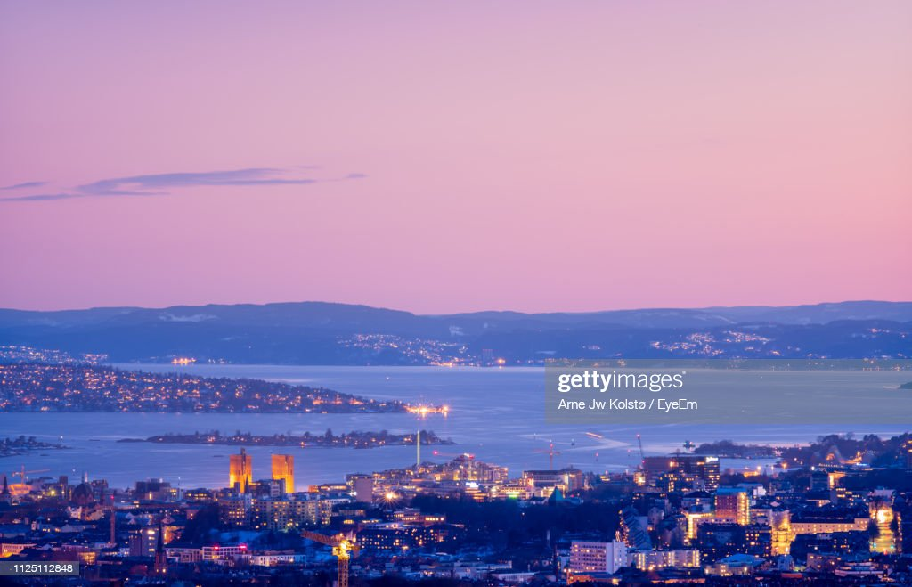 High Angle View Of Illuminated Buildings By Sea Against Sky At Sunset : Stock Photo