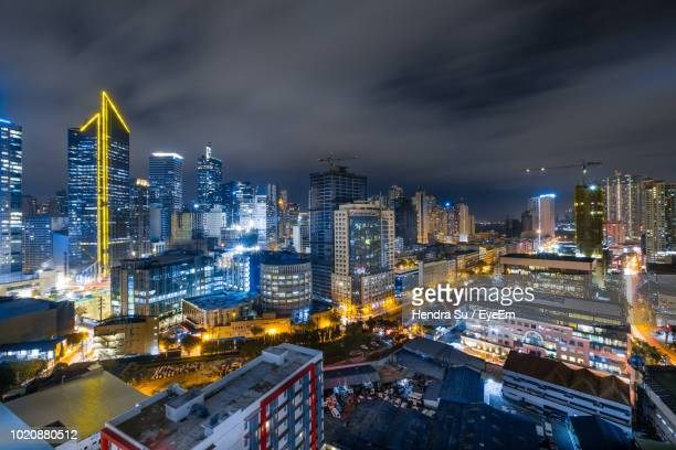 high angle view of illuminated buildings in city against sky - metro manila stock photos and pictures