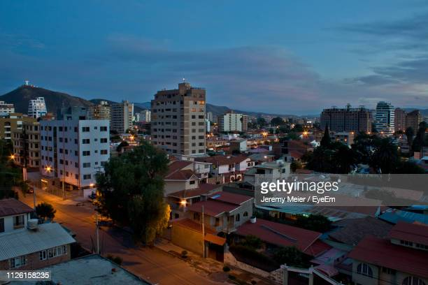high angle view of illuminated buildings in city at dusk - cochabamba stock pictures, royalty-free photos & images