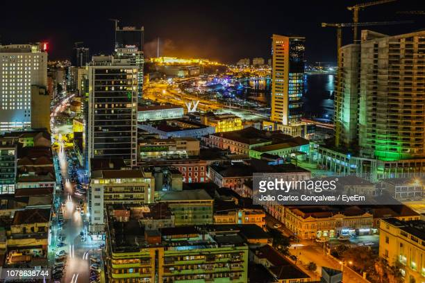 high angle view of illuminated buildings in city at night - angola stock pictures, royalty-free photos & images