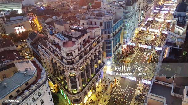 high angle view of illuminated buildings in city at night - nachtleben stock-fotos und bilder