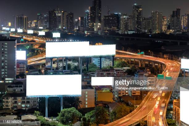 high angle view of illuminated buildings in city at night - billboard highway stock pictures, royalty-free photos & images