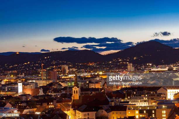 high angle view of illuminated buildings in city at night - graz stock photos and pictures