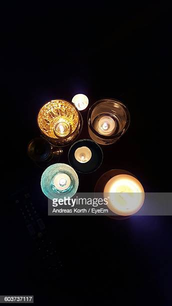 High Angle View Of Illuminated Candles Against Black Background