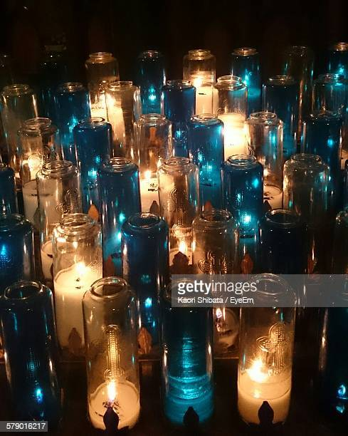 High Angle View Of Illuminated Candles In Glass Bottles