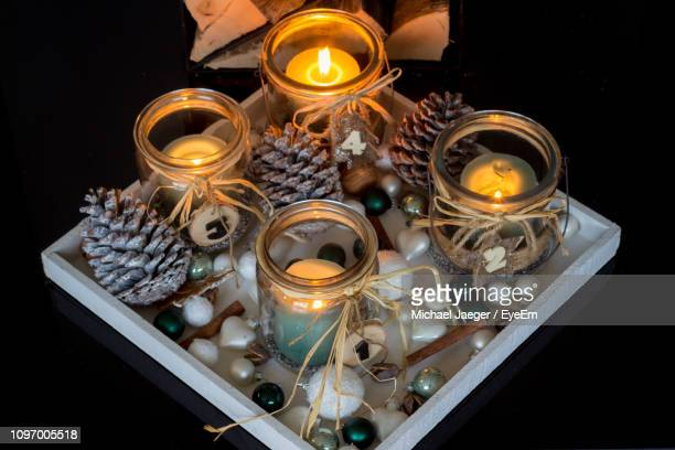 high angle view of illuminated candles in tray - michael jaeger stock pictures, royalty-free photos & images