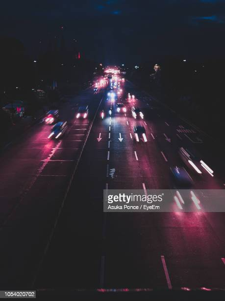 high angle view of illuminated cars moving on road at night - asuka stock pictures, royalty-free photos & images