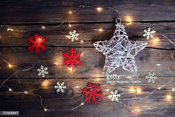 high angle view of illuminated christmas decorations on wooden table - christmas star stock photos and pictures