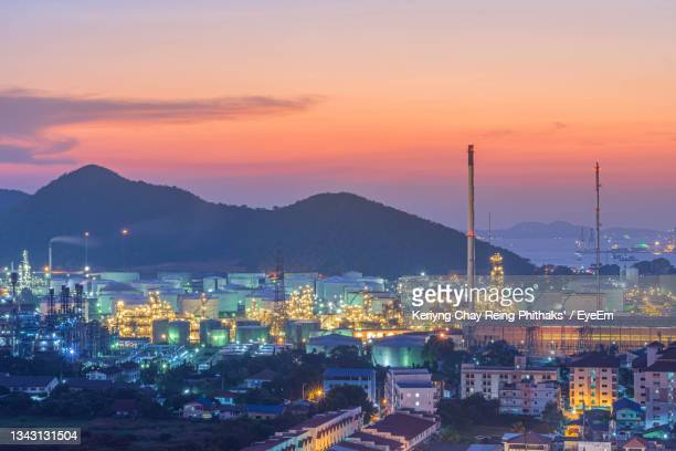 high angle view of illuminated city against sky at sunset - greenpeace stock pictures, royalty-free photos & images