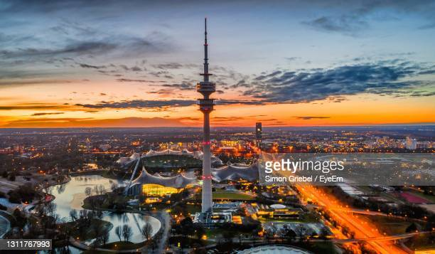 high angle view of illuminated city against sky during sunset - munich stock pictures, royalty-free photos & images
