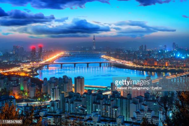 high angle view of illuminated city buildings against sky - south korea stock pictures, royalty-free photos & images